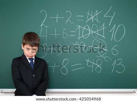 school boy decides examples math incorrect on chalkboard background, education concept - stock photo