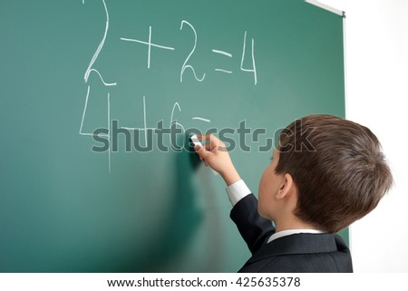 school boy decides examples math on chalkboard background, education exam concept - stock photo