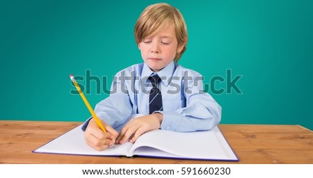 School boy doing homework at desk against green background