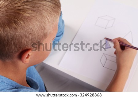 School Boy drawing ,coloring geometric shapes on paper with Pencil. Kid, homework,mathematics, education concept - stock photo