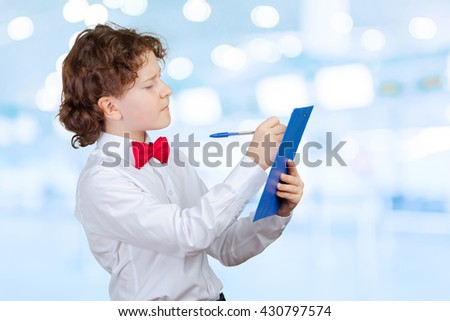 school boy in suit and blank paper sheet in clipboard