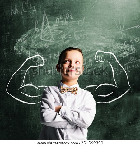 school boy is standing with strong hands on blackboard behind him - stock photo