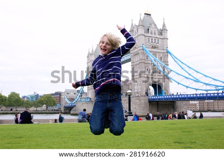 School boy jumping on the lawn in front of beautiful Tower Bridge and River Thames on a sunny summer day, London, UK. Happy caucasian tourist kind enjoying view during family trip to England. - stock photo