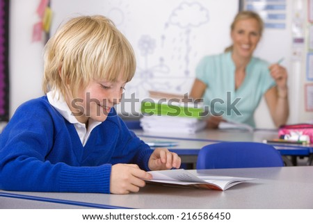School boy reading workbook in classroom - stock photo