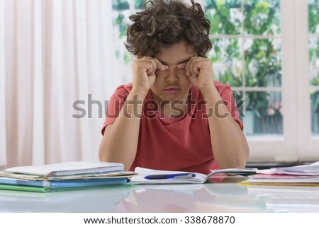 School boy rubbing eyes after long time homework - stock photo