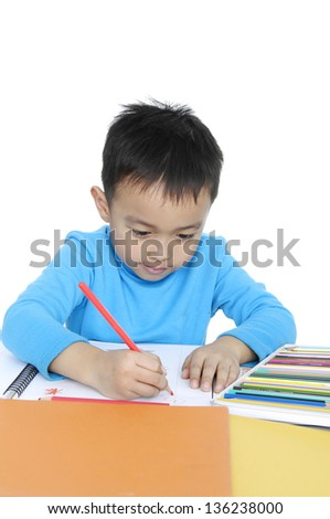 School boy sitting and writing in notebook. - stock photo