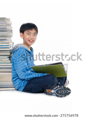 School boy sitting and writing in notebook.