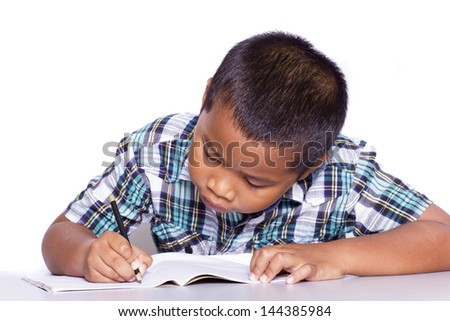 School boy sitting and writing in notebook over white background - stock photo