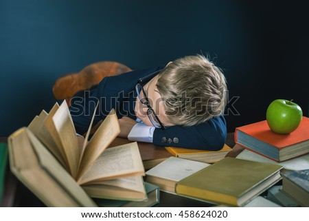 School boy sleeping at the table with many books and one green apple. Many homeworks or exam - is stress for little kids. Motivate your child to study a boring subject. Student. Pupil studying - stock photo