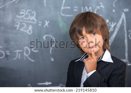 School boy trying to solve equations - stock photo