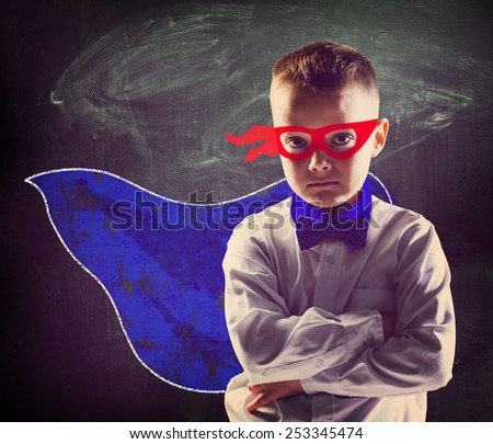 school boy wearing a superhero costume with blackboard behind him - stock photo
