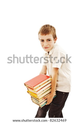 School boy with heavy stack of books - stock photo