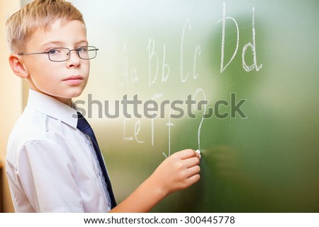 School boy writes English alphabet with chalk on a blackboard in school classroom. He looking at the camera and does not know continuation of the alphabet and wrote a question mark. - stock photo