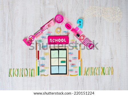School building composed by colorful stationery objects on the floor. - stock photo