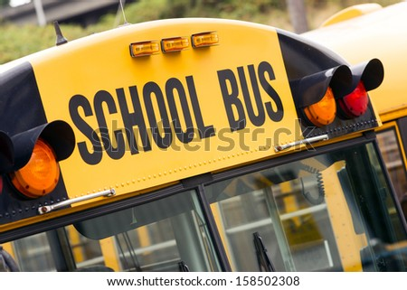 School bus children educational transport sitting in the parking lot waiting to be in service - stock photo