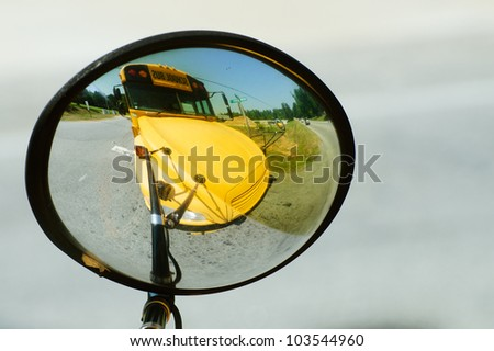 School bus reflected in its own wide angle safety mirror - stock photo
