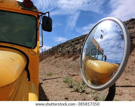 School bus reflected in side mirror in desert setting - landscape color photo - stock photo