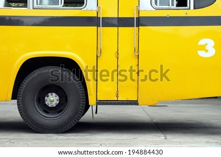 School bus side view, wing with a wheel, yellow bus. - stock photo