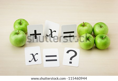 School card and apple with math problems on the table - stock photo