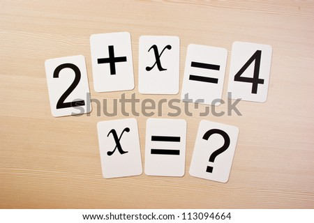School card  with math problems on the table - stock photo