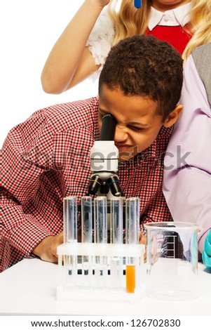School chemistry research - black eight years old boy looking to microscope - stock photo