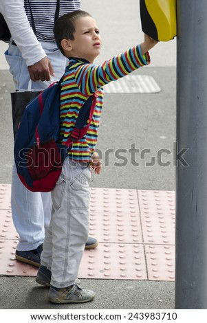 School child boy pressing a button on pedestrian road crossing. - stock photo