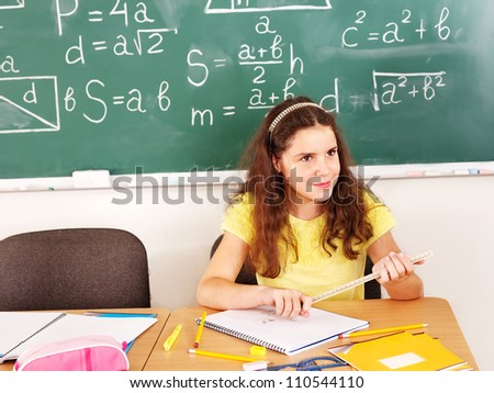 School child sitting on desk in classroom.