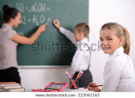 School child with teacher in classroom during lesson. concept of school
