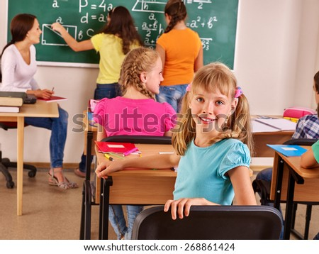 School child with teacher in classroom. Group people. - stock photo