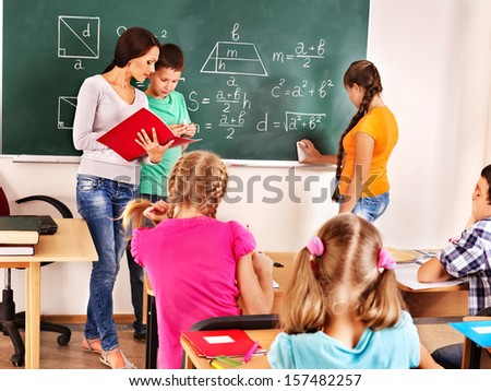 School child with teacher on math lesson.