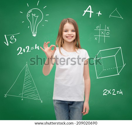 school, childhood, gesture and education concept - smiling little girl in white blank t-shirt showing ok sign - stock photo