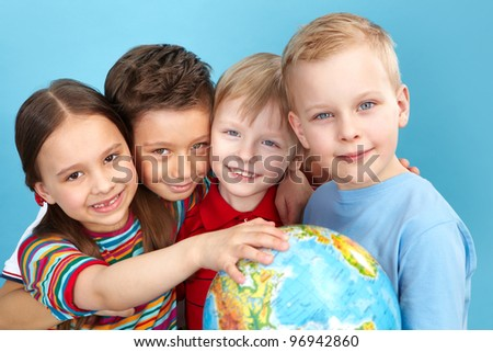 School children holding a globe looking at camera positively - stock photo