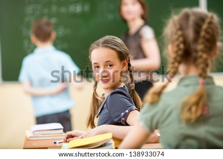 School children in classroom at lesson with teacher - stock photo