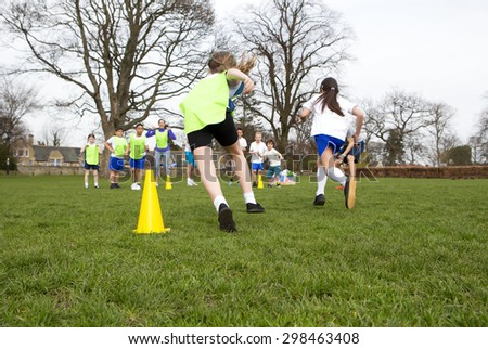 School children wearing sports uniform running around cones during a physical education session. - stock photo