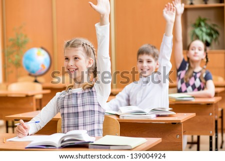 school children with raised hands at lesson in classroom - stock photo