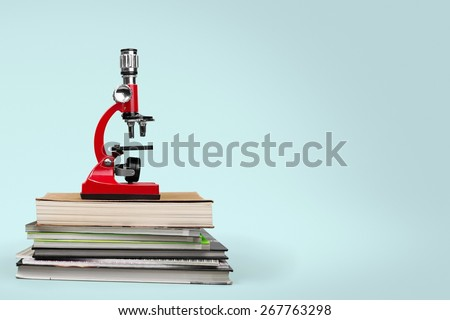School. Color photo of a microscope on stack of books - stock photo