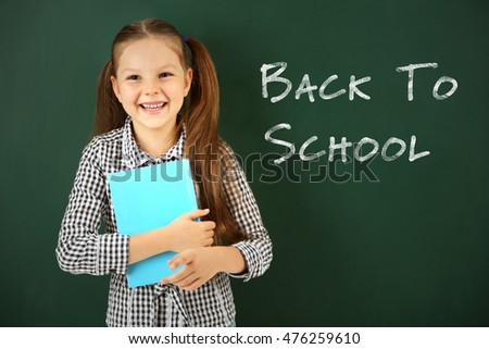 School concept. Cute girl holding book on blackboard background. Text back to school.