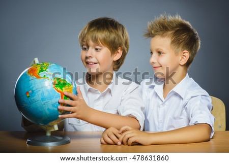school concept. Smiling happy boys sitting at desk and show on Globe