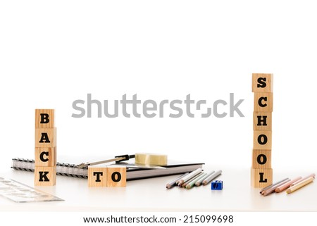 School concept with the words Back To School displayed on stacked wooden blocks with pencils, pencil crayons, rubber, sharpener and notebook depicting school stationery, central copyspace on white. - stock photo