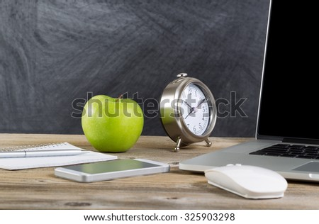 School desktop with laptop, mouse, clock, cell phone, notebook, pen and green apple in front of blackboard. Layout in horizontal format with copy space.  - stock photo