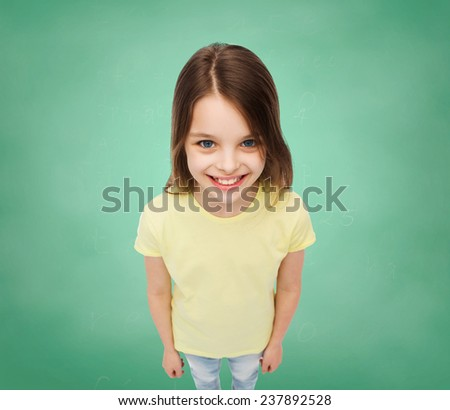 school, education, childhood and people concept - smiling little girl in blank t-shirt over green board background - stock photo