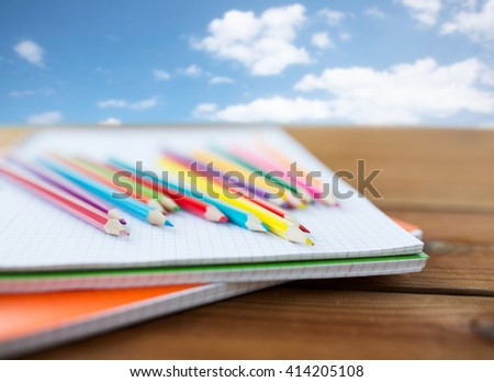 school, education, drawing and object concept - close up of crayons or color pencils on notebook paper over blue sky and clouds background - stock photo
