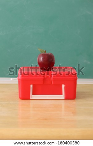 School education still life with apple on lunch box - stock photo