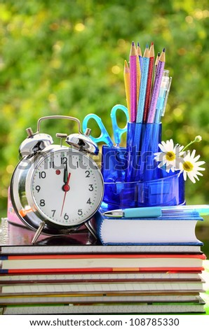 school equipment and alarm clock against green trees - stock photo