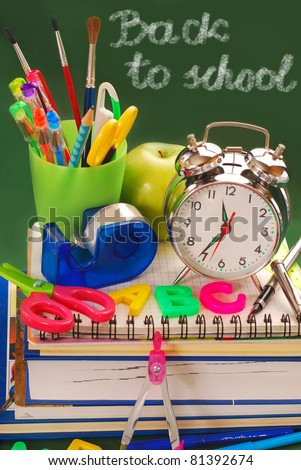 "school equipment ,retro alarm clock and ""back to school"" writen on green chalkboard - stock photo"