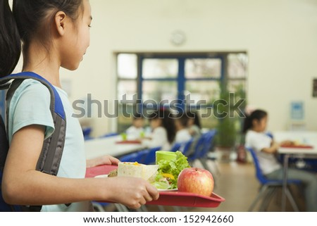 School girl holding food tray in school cafeteria - stock photo