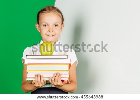 school girl in a school uniform holding a stack of books and green apple.. Learning and school concept. Image on chromakey background. - stock photo