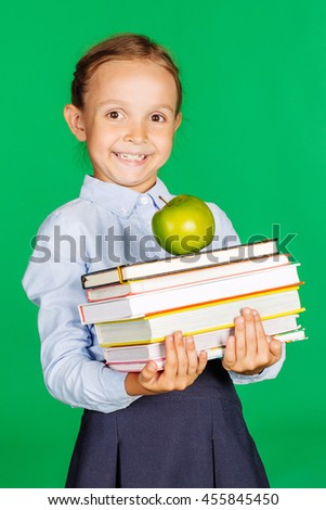 school girl in a school uniform holding a stack of books and green apple. Learning and school concept. Image on chromakey background. - stock photo