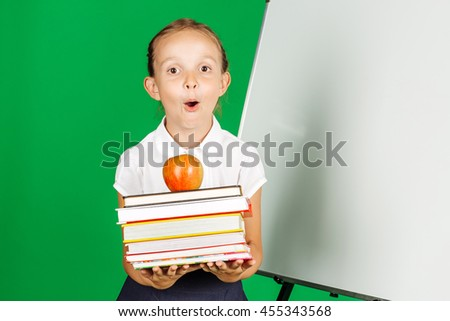 school girl in a school uniform holding a stack of books and red apple. Learning and school concept. Image on chromakey background. - stock photo