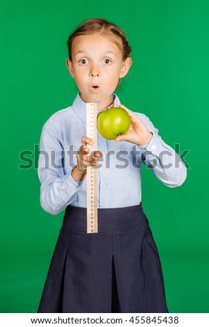 school girl in a school uniform with a green apple and ruler. Learning and school concept. Image on chromakey background. - stock photo